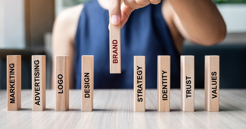 Businesswoman-hand-placing-or-pulling-wooden-dominoes-with-brand-text-and-marketing-advertising-logo